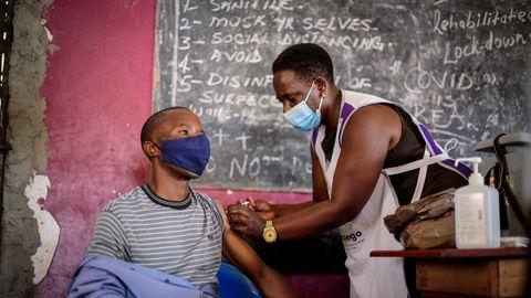 Uganda: Eine Krankenschwester verabreicht einem jungen Mann eine Impfung gegen das Coronavirus