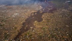 Dunkle Lavamassen fließen von der Cumbre Vieja herab und fressen sich durch die Landschaft
