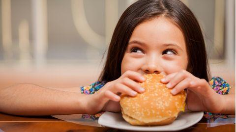 Ein Mädchen beißt in einen Burger