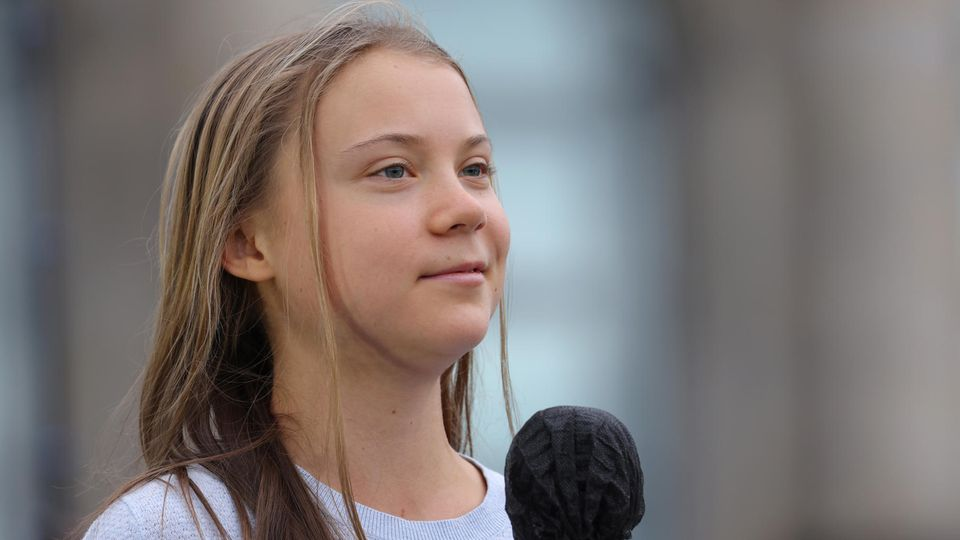 Eine junge weiße Frau mit langen, dunkelblonden Haaren lächelt leicht, während sie ein schwarzes Mikro hält