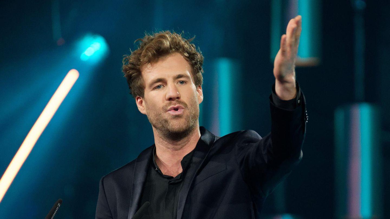 Ein weißer Mann mit dunkelblonden Locken und Drei-Tage-Bart steht im Jackett auf einer Bühne und zeigt mit dem linken Arm