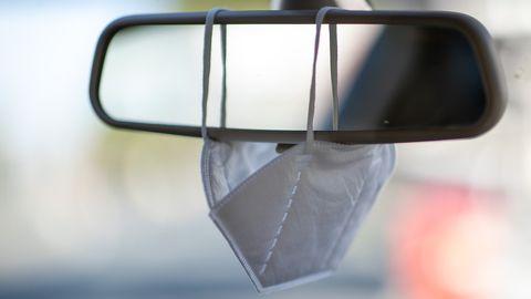 Eine FFP2-Maske hängt am Rückspiegel eines PkWs