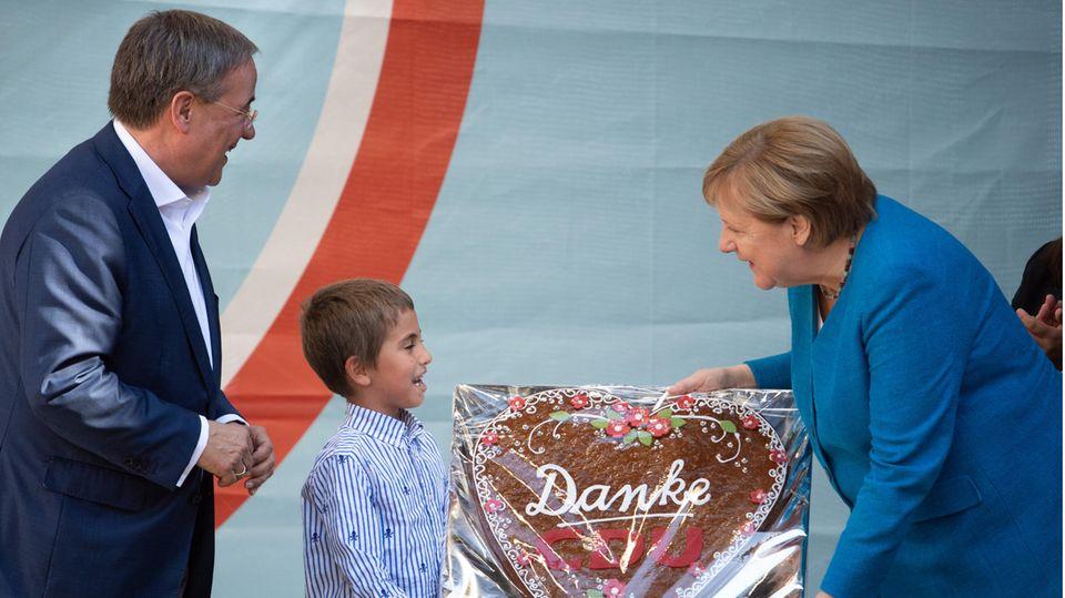 """Ein Junge übergibt ein Lebkuchenherz mit der Aufschrift """"Danke"""""""