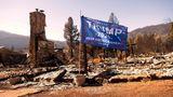 Eine Donald Trump-Flagge weht vor einem niedergebrannten Wohnhaus in Greenville, Kalifornien