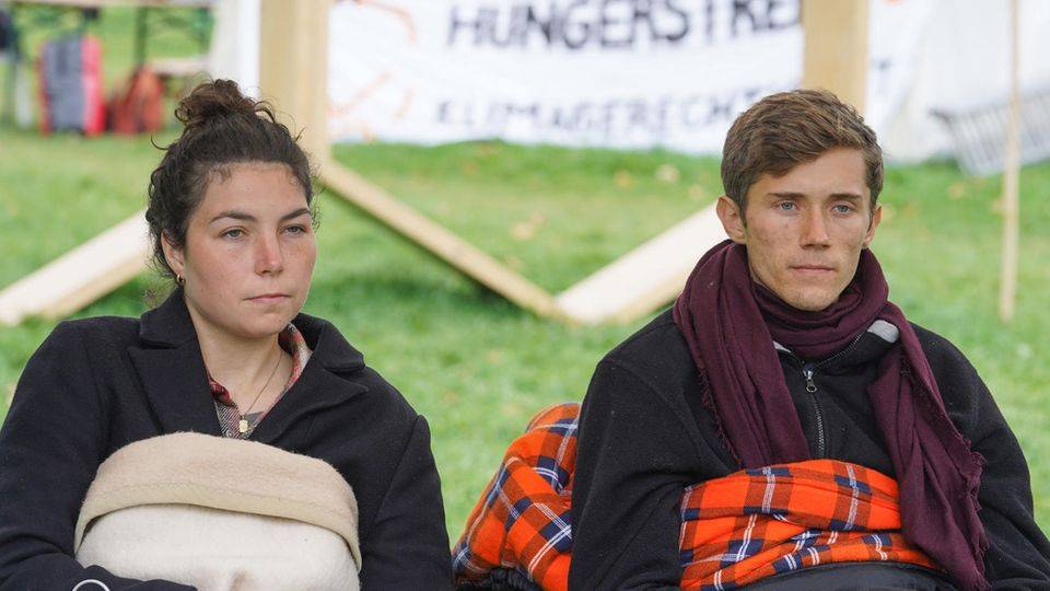 """Lea und Henning, beiden verbliebenen Teilnehmer des """"Hungerstreiks der letzten Generation"""", geben auf einer Pressekonferenz bekannt, dass sie ab sofort in einen trockenen Hungerstreik treten"""