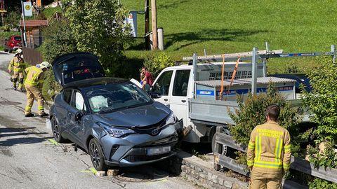 Ein demolierter dunkelblauer Pkw steht an einer kleinen Mauer. Feuerwehrleute in gelb räumen um den Wagen herum auf