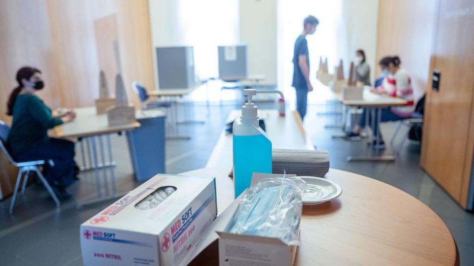Nordrhein-Westfalen, Kamen: Desinfektionsmittel und Masken liegen in einem Wahllokal bereit