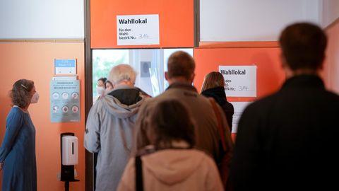 Wähler stehen in einer Schlange vor dem Wahllokal für die Bundestagswahl und die Wahl des Abgeordnetenhauses