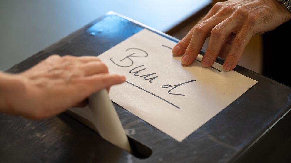"""Während eine Hand einen Wahlzettel in eine Wahlurne steckt, zieht eine andere einen Zettel mit """"Bund""""-Aufschrift vom Schlitz"""