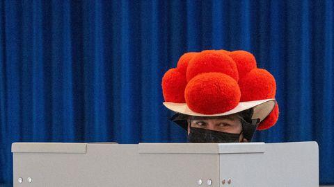 Über den grauen Sichtschutz einer Wahllkabine hinweg sieht man die Augen einer Frau unter der Krempe eines Bollenhutes