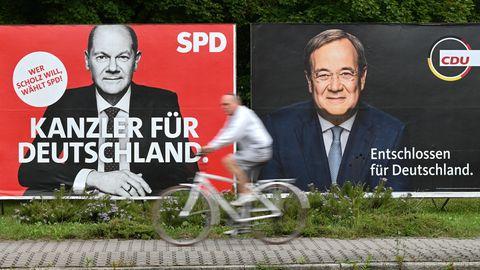 Ein Radfahrer fährt an großen Wahlplakaten mit den Spitzenkandidaten Olaf Scholz (SPD, l) und Armin Laschet (Union) vorbei