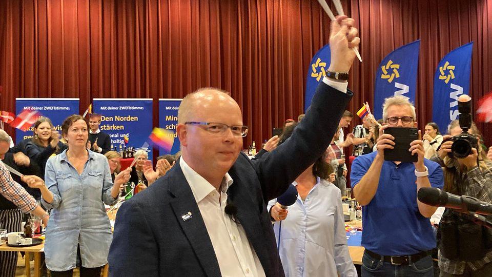 Stefan Seidler schwenkt auf der Wahlparty des SSW Fähnchen mit dem Dannebrog und den friesischen Farben