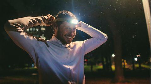 Stirnlampen beim Joggen: Junger Mann bereitet sich auf einen abendlich Lauf mit Stirnlampe vor