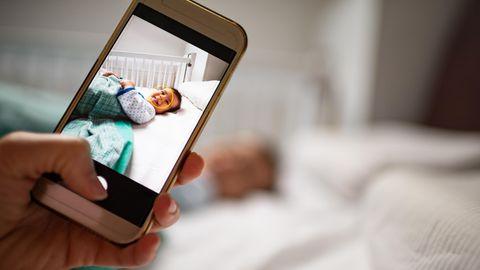 Mit dem Handy wird ein Foto vom Baby gemacht