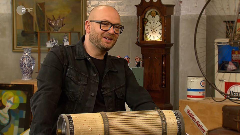 Bares-für-Rares-Experte Deutschmanek steht im Studio hinter dem Rechenzylinder