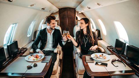 Konsumbedingter CO2-Ausstoß: Mann und Frau stoßen in einem Privatjet mit Champagner an