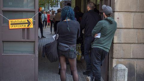 Menschen warten in einer Schlange vor einem Wahllokal im Berliner Stadtteil Prenzlauer Berg darauf, ihre Stimmen zur Bundestagswahl, der Abgeordnetenhauswahl und der Wahl der Bezirksvertretungen abgeben zu dürfen