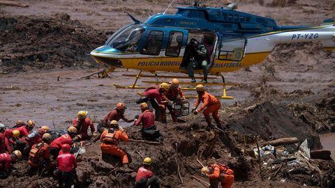 Feuerwehrleute und ein Helikopter bei der Dammbruch-Katastrophe in Brumadinho