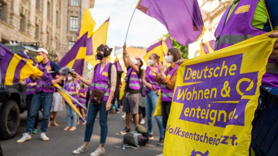 """Unterstützer der Initiative """"Deutsche Wohnen & Co. enteignen"""" schwenken im Juni in Berlin Fahnen"""