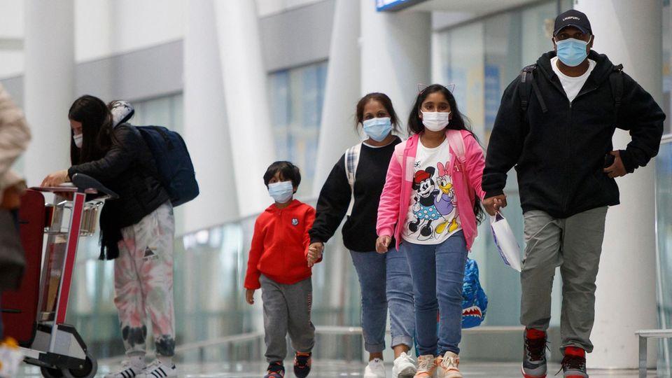 Fünf Personen in Freizeitkleidung und Mundschutz in einem Flughafengebäude