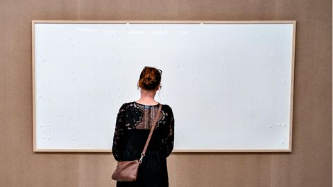 Eine Frau schaut auf ein leeres, weißes Bild im Kunsten Museum in Aalborg