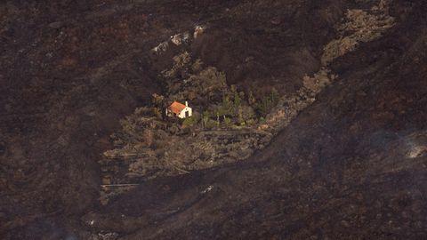 Ein Haus steht inmitten von Asche und Lava wie auf einer Insel