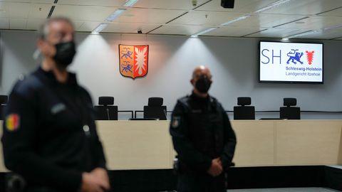 Justizbeamte mit Mundschutz stehen in Itzehoe in einem leeren Gerichtssaal
