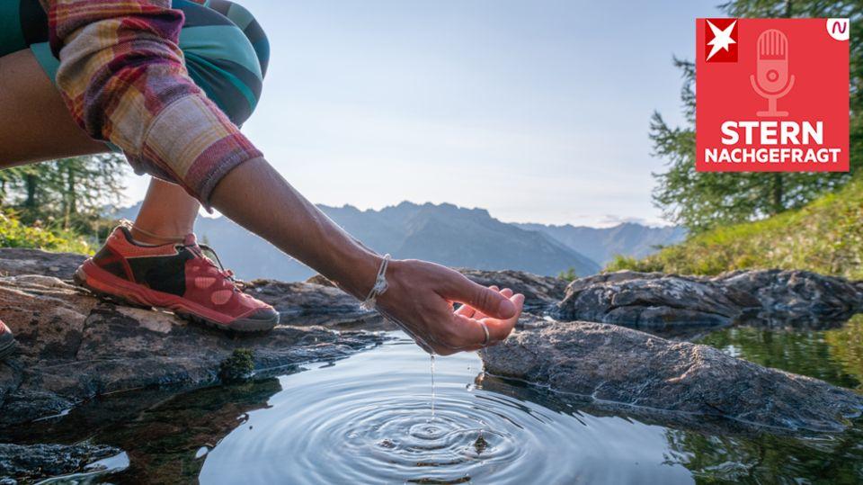 Eine Frau schöpft mit ihrer Hand Wasser aus einem Bergsee