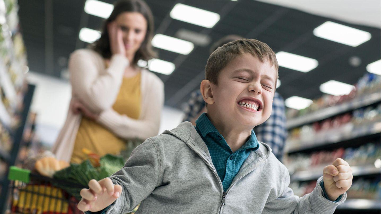 Kleiner Junge beim Einkaufen. Im Hintergrund fast sich seine Mutter an den Kopf.