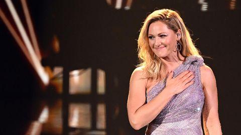 Helene Fischer steht im schulterfreien Paillettenkleid auf einer TV-Bühne, lächelt und legt die rechte Hand aufs Herz