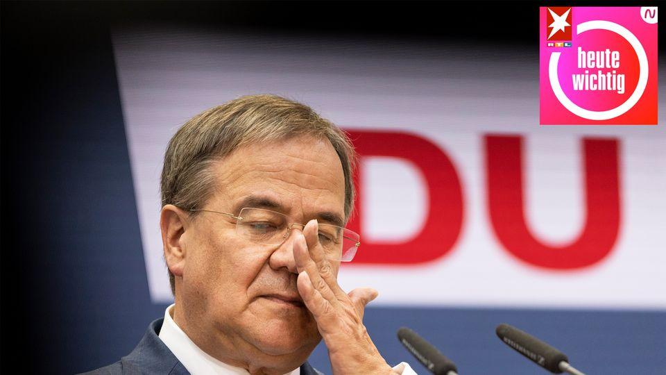 Ein älterer weißer Mann im Anzug und mit randloser Brille wischt sich mit der linken Hand übers Gesicht
