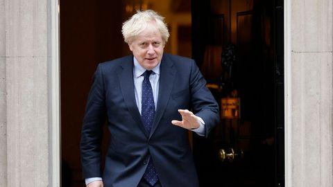 Boris Johnson tritt aus einer Tür heraus und winkt
