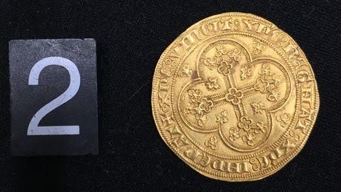 Eine Münze liegt auf einen schwarzen Untergrund, links daneben die Ziffer 2
