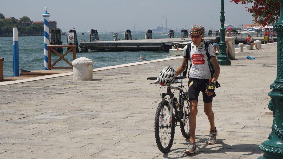 Mann schiebt sein Fahrrad durch die Altstadt von Venedig