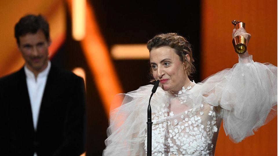 Eine dunkelblonde weiße Frau regt ihren linken Arm mit einer goldenen Trophäe hoch. Sie trägt ein halbtransparentes weißes Kleid