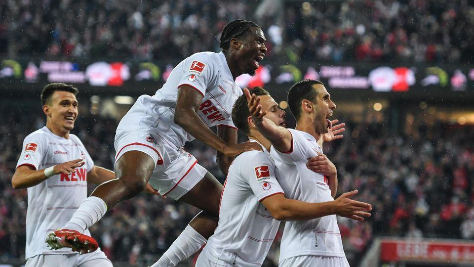 Eine Horde Fußballer in weißen Trikots und Hosen jubelt hinter einem Mitspieler, der seine Arme ausbreitet