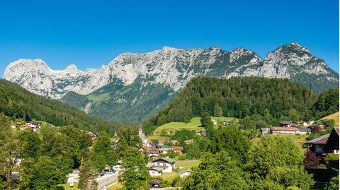 Zwischen Wiesen ist ein Bergdorf mit weißen Häusern und Kirche zu sehen, im Hintergrund eine Bergkette
