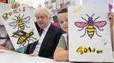 """Manchester, Großbritannien. """"Der große Boris möchte aus dem Kinderparadies abgeholt werden!"""" Premier Boris Johnson hält seine Version der Manchester Bee– eine Arbeiter-Biene, die als Symbol für die Stadt und ihre Bewohner gilt – in die Kamera. Der Regierungschef besuchtdas Jugendcamp des Parteikongresses seiner Conservative and Unionist Party. Der Parteitag der Tories wird durch die Versorgungskrise im Königreich bestimmt werden."""