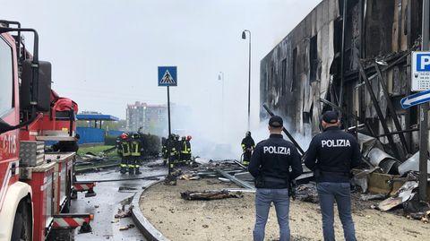 Feuerwehrleute und Polizisten stehen an der Absturzstelle eines Flugzeugs in San Donato, einem Vorort von Mailand