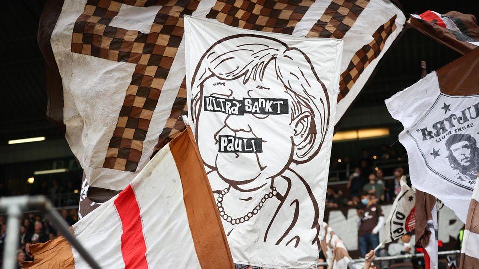 Ein Banner mit einer Zeichnung von Angela Merkel im Fanblock des FC St. Pauli