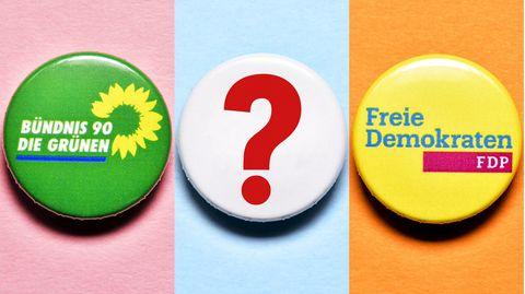 Partei-Anstecker von der FDP und den Grünen mit Fragezeichen