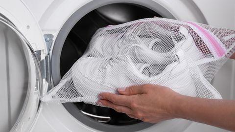Paar schmutzige weiße Turnschuhe in der Waschmaschine
