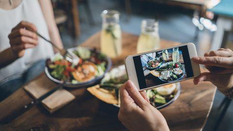 Frau macht Foto von ihrem Essen im Restaurant