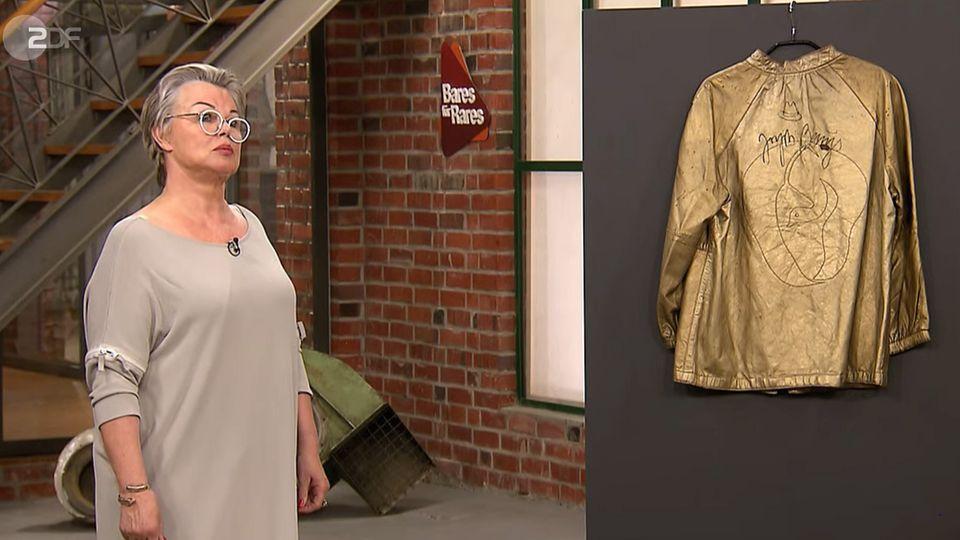 Monika Vonknechten steht im Studio von Bares für Rares neben ihrer Jacke