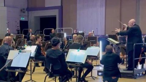 Ein Orchester sitzt im Halbkreis um ein Dirigentenpult. Auf dem Pult steht ein Senior, der mit ausgestreckten Armen dirigiert.