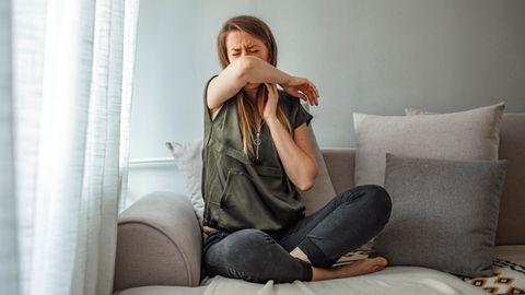 Symptome von Corona, Erkältung, Grippe: Eine Frau sitzt auf einem Sofa und hustet