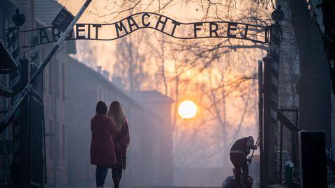 Besucher stehen vor dem Eingangstor von Auschwitz-Birkenau
