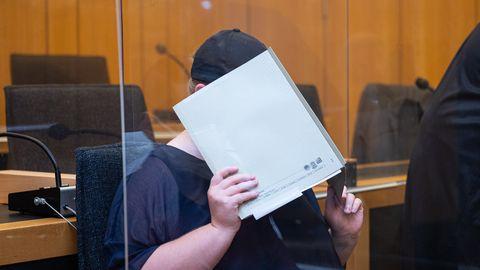 Mutter eines Opfers sitzt im Landgericht Münster und verdeckt ihr Gesicht mit einer Mappe