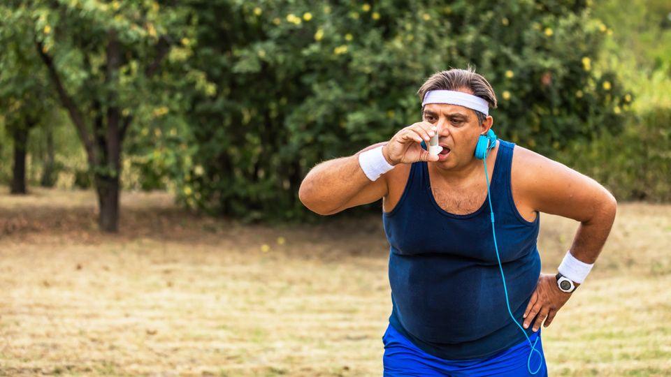 Ein übergewichtiger Mann ist bei Sport außer Atem geraten