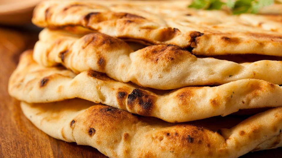 Naan-Brot liegt übereinander gestapelt auf einem Holztisch